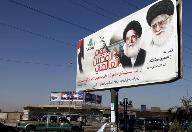 A poster depicting Iran's supreme leader, Grand Ayatollah Ali Khamenei (right), and Ayatollah Mohammed Sadiq al-Sadr, late father of the radical anti-U.S. cleric Muqtada al-Sadr, towers over a Baghdad street on Sunday, Sept. 16, 2012. (AP Photo/Karim Kadim)