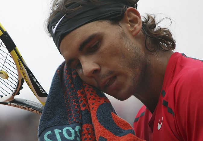 FILE - This June 10, 2012 file photo shows Rafael Nadal wiping his face as he plays Serbia's Novak Djokovic during their men's final match in the French Open tennis tournament at Roland Garros stadium in Paris. Nadal still has no timetable for his return from a knee injury. The Spaniard hasn't played since losing in the second round of Wimbledon in June to little-known Lukas Rosol.  (AP Photo/David Vincent, File)