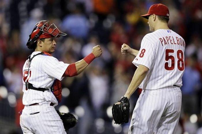 Philadelphia Phillies catcher Carlos Ruiz, left, and relief pitcher Jonathan Papelbon celebrate their 6-3 win in a baseball game against the Washington Nationals, Tuesday, Sept. 25, 2012, in Philadelphia. (AP Photo/Matt Slocum)