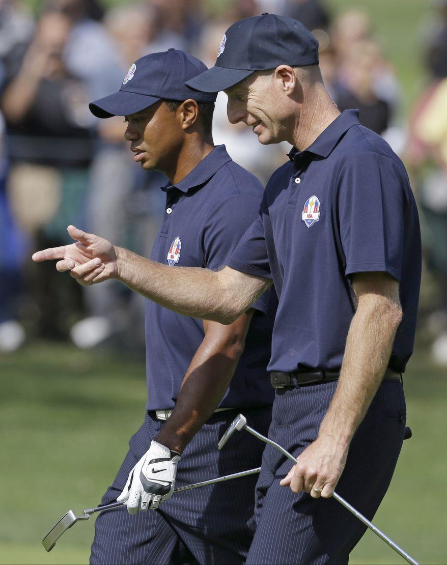 USA's Jim Furyk talks to Tiger Woods at the Ryder Cup PGA golf tournament Tuesday, Sept. 25, 2012, at the Medinah Country Club in Medinah, Ill. (AP Photo/Chris Carlson)