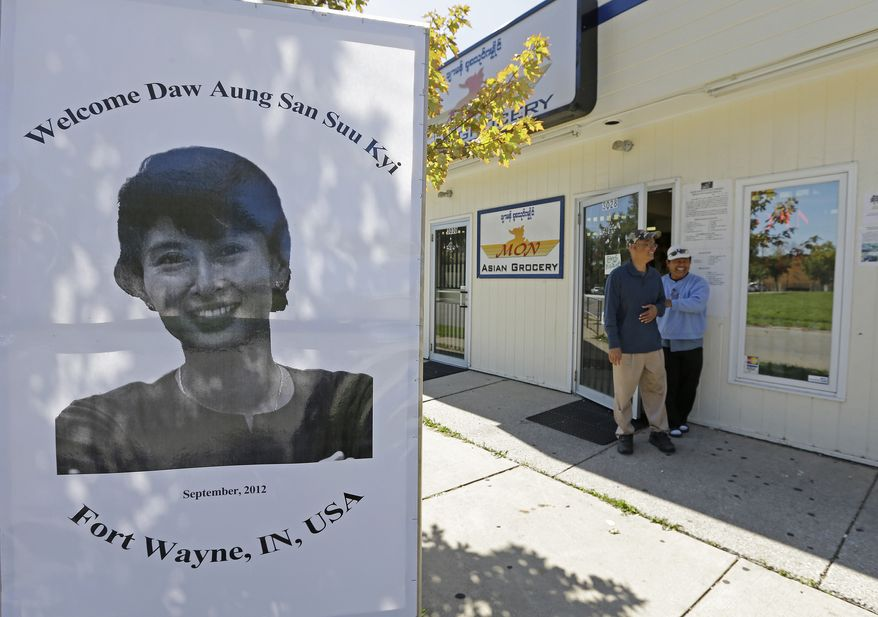 Nai Sike (left) and Paung Pakong walk out of Mr. Sike's grocery store, where a display of Myanmar democracy leader Aung San Suu Kyi is displayed out front, on Thursday, Sept. 20, 2012, in Fort Wayne, Ind. (AP Photo/Darron Cummings)