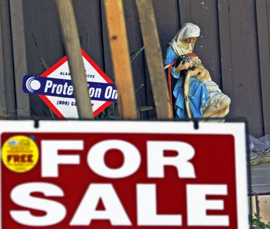 """A religious statuette is displayed with a """"For Sale"""" sign on the front porch of the home of Nakoula Basseley Nakoula, the man who made the film """"Innocence of Muslims,"""" in Cerritos, Calif., on Tuesday, Sept. 25, 2012. (AP Photo/Reed Saxon)"""