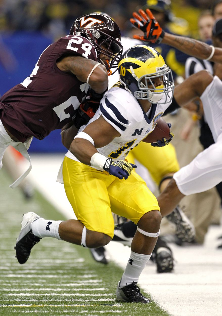 Michigan wide receiver Jeremy Gallon (10) is forced out of bounds by Virginia Tech linebacker Tariq Edwards (24) during the second quarter of the Sugar Bowl NCAA college football game in New Orleans, Tuesday, Jan. 3, 2012. (AP Photo/Dave Martin)