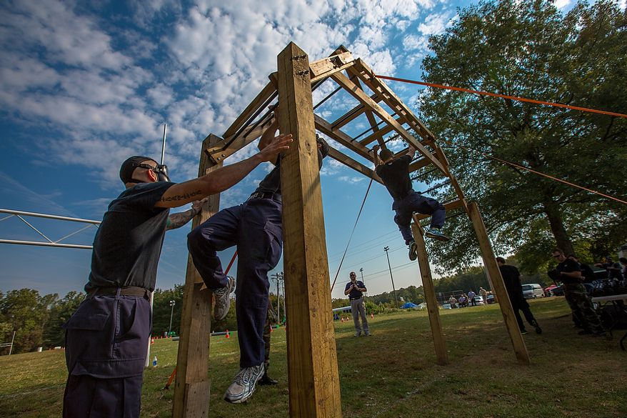 Metro Transit Officers, from Washington D.C., use upper body strength to cross the monkey bars while wearing gas masks at the Iron Team Endurance Competition in Laurel, MD., Wednesday, September 26, 2012. The competition is hosted by the Prince George's County Police where teams from all over the east coast, including the Marines, compete in a grueling physical endurance challenge.(Andrew S. Geraci/The Washington Times)