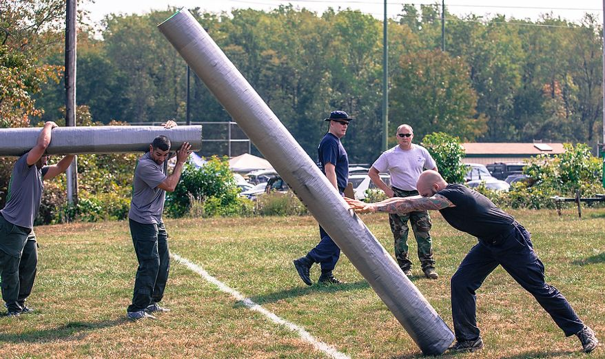 Officer Matt Harbison, assigned to Metro Transit in Washington D.C., flips a log weighing hundreds of pounds across the finish line at the Iron Team Endurance Competition in Laurel, MD., Wednesday, September 26, 2012. The competition is hosted by the Prince George's County Police where teams from all over the east coast, including the Marines, compete in a grueling physical endurance challenge.(Andrew S. Geraci/The Washington Times)