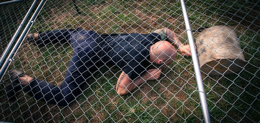 Officer Matt Harbison, assigned to Metro Transit in Washington D.C., crawls under a low-laying fence while pushing a hundred pound block of cement in front of him at the Iron Team Endurance Competition in Laurel, MD., Wednesday, September 26, 2012. The competition is hosted by the Prince George's County Police where teams from all over the east coast, including the Marines, compete in a grueling physical endurance challenge.(Andrew S. Geraci/The Washington Times)