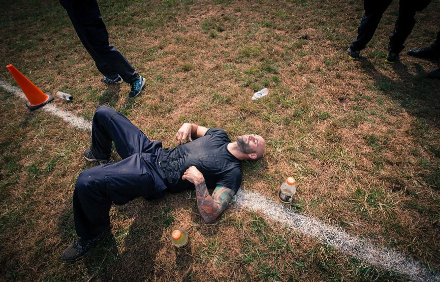 Officer Matt Harbison, assigned to Metro Transit in Washington D.C., lays down in exhaustion after lifting cement blocks and flipping logs at the Iron Team Endurance Competition in Laurel, MD., Wednesday, September 26, 2012. The competition is hosted by the Prince George's County Police where teams from all over the east coast, including the Marines, compete in a grueling physical endurance challenge.(Andrew S. Geraci/The Washington Times)