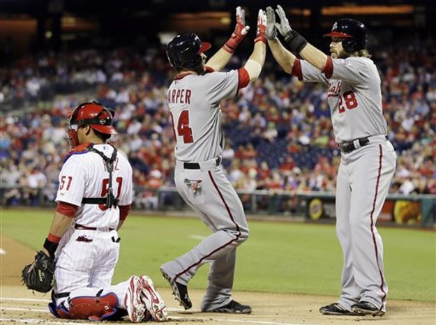 Washington Nationals' Bryce Harper, center, and Jayson Werth, right, celebrate after Harper's two-run home run off Philadelphia Phillies starting pitcher Kyle Kendrick in the first inning of a baseball game, Wednesday, Sept. 26, 2012, in Philadelphia. Washington won 8-4. (AP Photo/Matt Slocum)