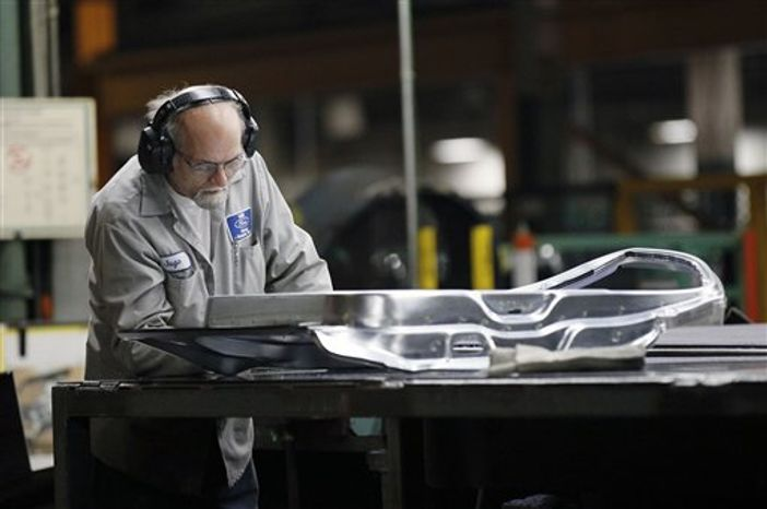 ** FILE ** In this Wednesday, April 4, 2012, photo, an auto worker at the Ford Stamping Plant inspects the inner door panel in Chicago Heights, Ill. (AP Photo/Charles Rex Arbogast)