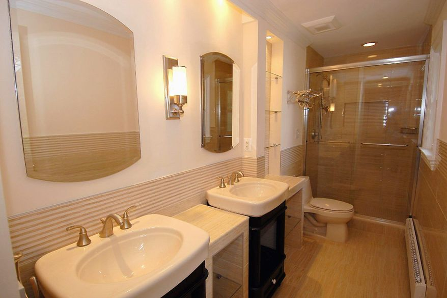 The master bath has been remodeled with European flair, and includes two vanities with deep sinks, extra storage space, a linen closet and a lighted shower area.