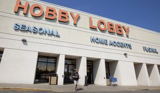 ** FILE ** A woman leaves a Hobby Lobby store in Little Rock, Ark., on Sept. 12, 2012. (Associated Press)