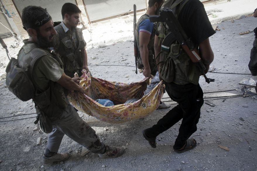 Free Syrian Army fighters carry the body of a comrade away from the front line during clashes against Syrian army forces in Aleppo, Syria, on Wednesday, Sept. 26, 2012. (AP Photo/Manu Brabo)