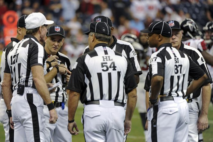 **FILE** NFL officials confer Dec. 4, 2011, in the fourth quarter of a game between the Atlanta Falcons and Houston Texans in Houston. (Associated Press)