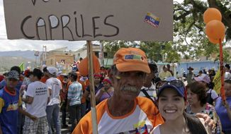 "A man and his daughter pose Sept. 1, 2012, with a poster that reads in Spanish, ""I'm a socialist and will vote for Capriles,"" at a campaign rally in Miranda, Venezuela. A segment of President Hugo Chavez supporters have been turning away from the president and considering opposition presidential candidate Henrique Capriles. (Associated Press)"
