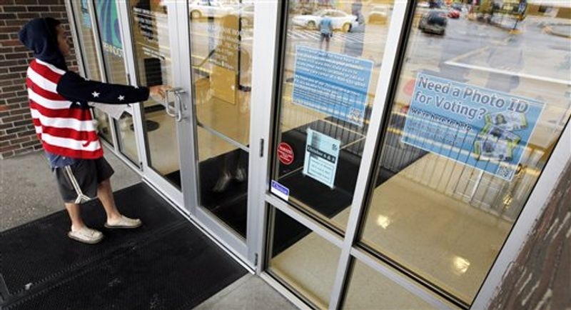** FILE ** A man heads into the the Penndot Drivers License Center in Butler, Pa., on Wednesday, Sept. 26, 2012, near a sign telling of the requirement for voters to show an acceptable photo ID to vote. (AP Photo/Keith Srakocic)
