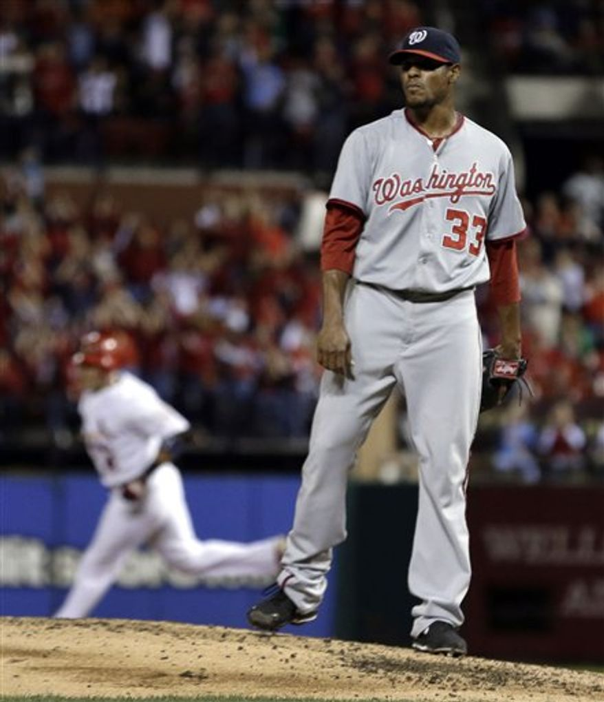 St. Louis Cardinals' Yadier Molina, left, rounds the bases after hitting a two-run home run off Washington Nationals starting pitcher Edwin Jackson during the second inning of a baseball game Friday, Sept. 28, 2012, in St. Louis. (AP Photo/Jeff Roberson)
