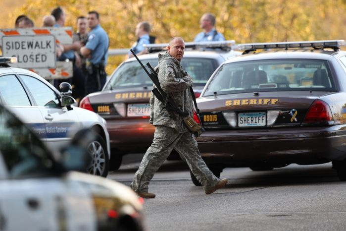 An officer walks through the area as police investigate a shooting at Accent Signage Systems on the north side of Minneapolis on Sept. 27, 2012. Police say at least two people were killed and four others wounded. (Associated Press/The Star Tribune, Renee Jones Schneider)