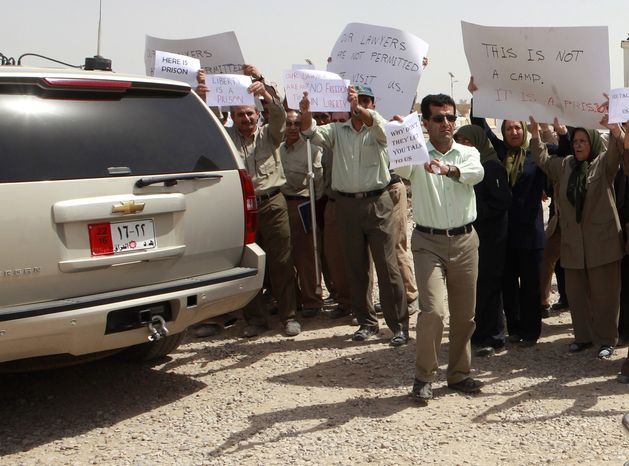 **FILE** Members of the Mujahedeen-e-Khalq organization chant slogans and hold banners during a tour organized by the Iraqi government for foreign diplomats in Baghdad on Sept. 11, 2012. (Associated Press)