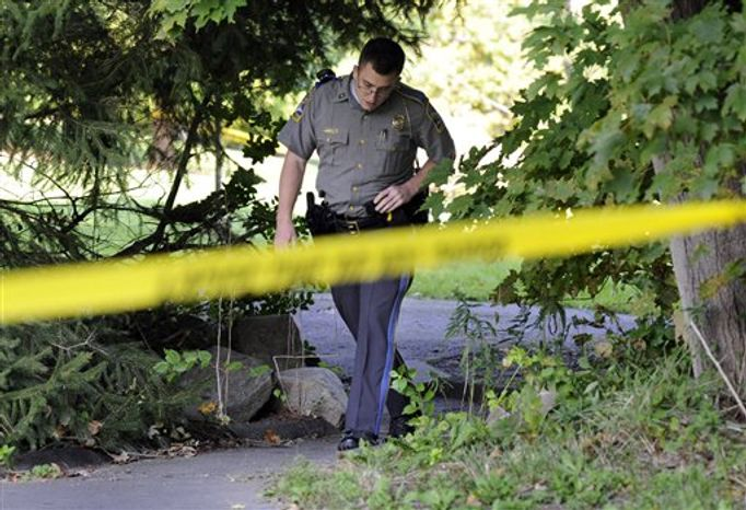 State Trooper Matt Losh emerges from the backyard of a home on Meeting House Hill Circle in New Fairfield, Conn., where a fatal shooting took place, Thursday, Sept. 27, 2012. A Connecticut man fatally shot a masked teenager in self-defense during what appeared to be an attempted burglary early Thursday morning, then discovered that he had killed his son, state police said. (AP Photo/The News-Times, Carol Kaliff)