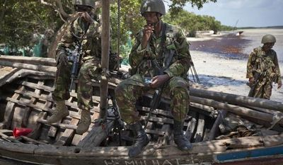 **FILE** Kenyan army soldiers sit Dec. 14, 2011, on a currently unused fishing boat on the white sand shore of the seaside town of Bur Garbo, Somalia. (Associated Press)
