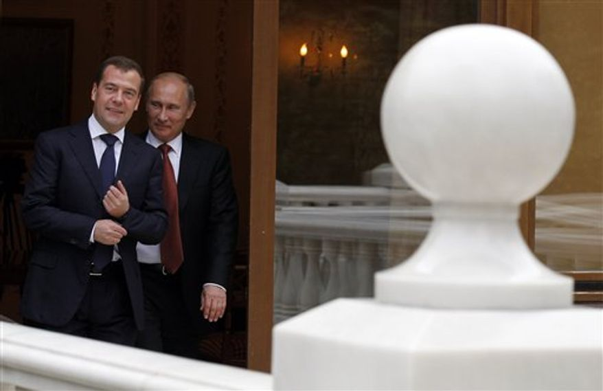 Russian President Vladimir Putin and Russian Prime Minister Dmitry Medvedev, left, stroll at the Novo-Ogaryovo residence outside Moscow, Thursday, Sept. 27, 2012. (AP Photo/RIA-Novosti, Dmitry Astakhov, Government Press Service)