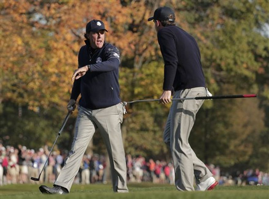 USA's Phil Mickelson, left, is congratulated by Keegan Bradley after making a putt on the fifth hole during a foursomes match at the Ryder Cup PGA golf tournament Saturday, Sept. 29, 2012, at the Medinah Country Club in Medinah, Ill. (AP Photo/Charlie Riedel)