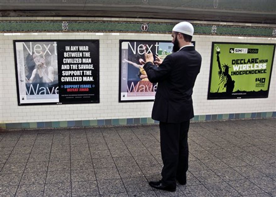 Cyrus McGoldrick, advocacy director for the Council on American-Islamic Relations, makes a photo with his cell phone of an anti-Muslim poster on Monday, Sept. 24, 2012, in New York's Times Square subway station. A federal court forced the Metropolitan Transportation Authority to run the ad by blogger Pamela Geller, executive director of the American Freedom Defense Initiative, saying it was protected speech under the First Amendment. (AP Photo/Bebeto Matthews) **FILE**