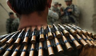 ** FILE ** An Afghan National Army soldier wears an ammunition belt around his neck during a joint patrol with U.S. Army soldiers from Bravo Company, 2nd Battalion of the 508 Parachute Infantry Regiment of the 82nd Airborne, in the volatile Arghandab Valley outside Kandahar, Afghanistan, in July 2010. (AP Photo/Kevin Frayer)
