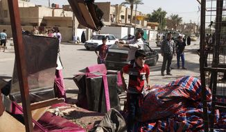 ** FILE ** Iraqis inspect the scene of a car bombing in Baghdad on Sunday, Sept. 30, 2012. (AP Photo/Karim Kadim)