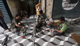 ** FILE ** Free Syrian Army fighters drink tea next to closed shops in the souk of the old city of Aleppo, Syria, on Monday, Sept. 24, 2012. (AP Photo/Hussein Malla)