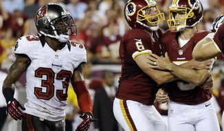 Washington Redskins kicker Billy Cundiff, right, celebrates with holder Sav Rocca, center, after making winning 41-yard field goal during the final seconds of the fourth quarter of an NFL football game against the Tampa Bay Buccaneers, Sunday, Sept. 30, 2012, in Tampa, Fla. At left is Buccaneers defensive back Brandon McDonald. Washington won 24-22. (AP Photo/Chris O'Meara)
