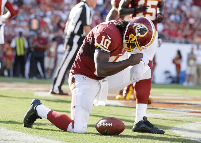 Washington Redskins quarterback Robert Griffin III (10) celebrates a touchdown during an NFL game between the Redskins and the Tampa Bay Buccaneers.  (AP Photo/Margaret Bowles)