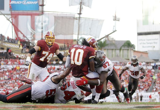 Tampa Bay Buccaneers defensive end George Johnson (97) sacks Washington Redskins quarterback Robert Griffin III (10) during an NFL game.   (AP Photo/Margaret Bowles)