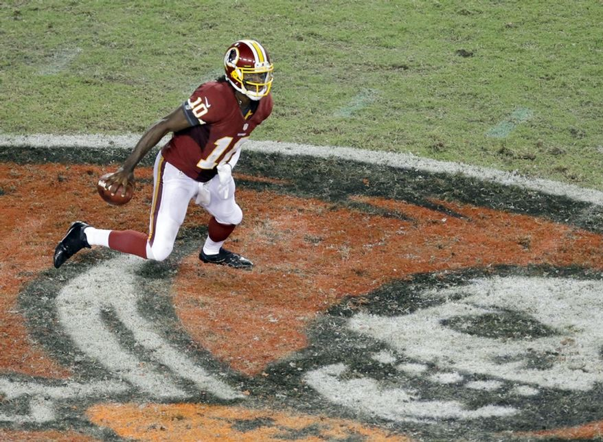 Washington Redskins quarterback Robert Griffin III (10) looks downfield for a receiver during an NFL game between the Redskins and the Tampa Bay Buccaneers.   (AP Photo/Margaret Bowles)