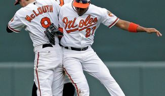 Orioles outfielders Nate McLouth, Adam Jones and Endy Chavez celebrate after a 6-3 win over Boston at Camden Yards on Sunday. Baltimore clinched at least a wild-card berth in the AL playoffs. (Associated Press)
