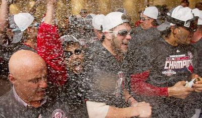 Andrew Harnik/the washington times CELEBRATE, CELEBRATE: The Washington Nationals whoop it up in the clubhouse Monday night after becoming the National League East Division champs by virtue of the Pittsburgh Pirates beating the Atlanta Braves. But the Nats lost their game with Philadelphia 2-0.