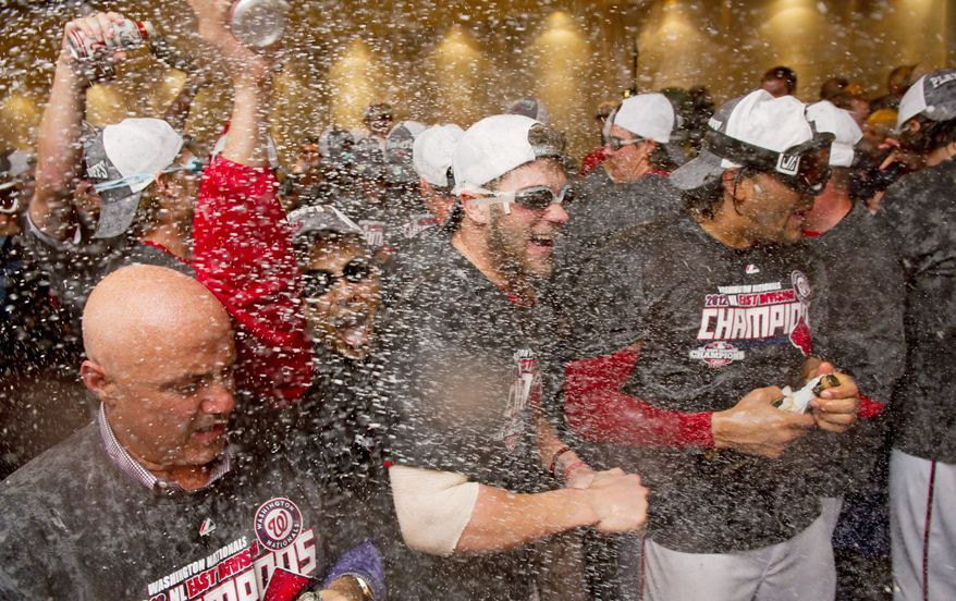 The Washington Nationals whoop it up in the clubhouse Monday night after becoming the National League East Division champs by virtue of the Pittsburgh Pirates beating the Atlanta Braves. But the Nats lost their game with Philadelphia 2-0. (Andrew Harnik/The Washington Times)