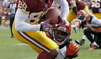 Washington Redskins wide receiver Santana Moss drags Cincinnati Bengals cornerback Adam Jones across the goal line for a touchdown during the second half of an NFL football game in Landover, Md., Sunday, Sept. 23, 2012. (AP Photo/Alex Brandon)