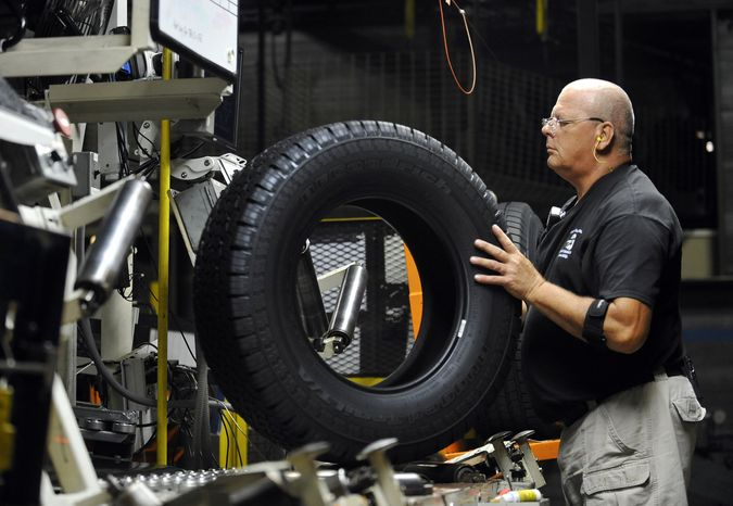 Inspector Buddy Rice checks for tire defects at a Michelin manufacturing plant in Greenville, S.C., on Tuesday, July 24, 2012. (AP Photo/Rainier Ehrhardt)