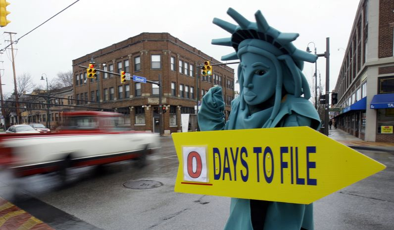 **FILE** Max Martinez, dressed as the Statue of Liberty, tries to alert motorists on April 18, 2011, the final day to file taxes for 2010. (Associated Press)