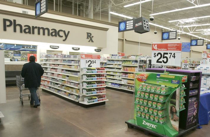 FILE - In this Feb. 20, 2008, file photo, a shopper walks toward the pharmacy at a Little Rock, Ark., Wal-Mart store. (AP Photo/Danny Johnston, File)
