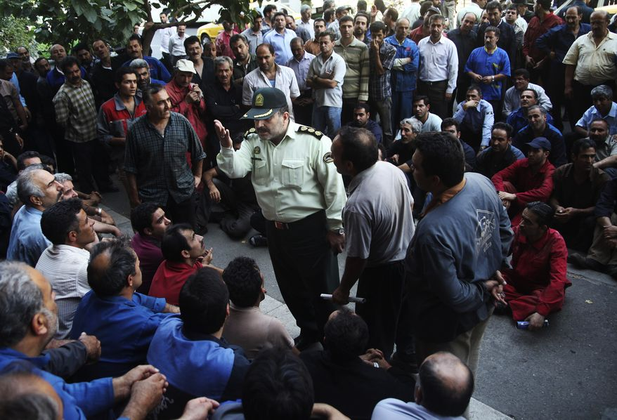 **FILE** A police colonel (center) talks with a group of Iranian workers Aug. 14, 2012, during their protest in front of the Industrial Ministry building in Tehran to demand their delayed salaries. (Associated Press)