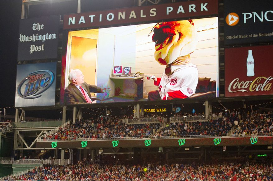 Sen. John McCain (R-Ariz.) gives Nationals President Teddy Roosevelt a pep talk on the jumbo screen before the president's race as the Washington Nationals play the Philadelphia Phillies. (Andrew Harnik/The Washington Times)