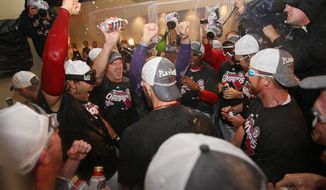 The Washington Nationals celebrate after clinching division champ with a lose to the Philadelphia Phillies but win by Pittsburg Pirates over the Atlanta Braves at Nationals Ballpark. (Craig Bisacre/The Washington Times)