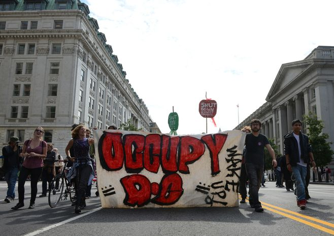 """The Occupy movement marches on Washington, D.C. on the one-year anniversary of Occupy D.C., Monday, Oct. 1, 2012. """"Real change takes time, even generations,"""" said one occupier. Another said that they are now changing their tactic from long-term occupation to short bursts of protests so that occupiers can go to work and earn a living. (Barbara L. Salisbury/The Washington Times)"""