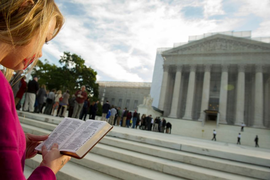 ** FILE ** A woman holds a Bible while standing in silent prayer on the steps of the Supreme Court on Oct. 1, 2012, before the justices return to the bench for another term. (Rod Lamkey Jr./The Washington Times)