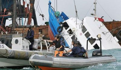 Associated Press Police officers guard the partially submerged Lamma IV after it collided with a ferry off the southwestern coast of Hong Kong on Tuesday, killing 38 passengers on a holiday outing and injuring dozens of others.