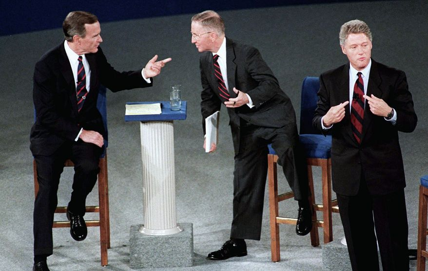 President George H.W. Bush talks with independent candidate H. Ross Perot (center) as Democratic candidate Bill Clinton stands aside at the end of their second debate. (Associated Press/File)