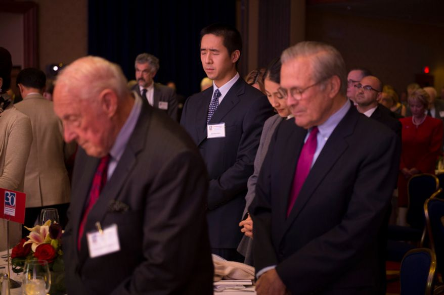 The Rev. Hyung Jin Moon (center) stands during a prayer at the evening banquet as part of the 30th anniversary celebration of The Washington Times at the Marriott Wardman Park Hotel in Washington, D.C., Tuesday, Oct. 2, 2012. (Rod Lamkey Jr./The Washington Times)