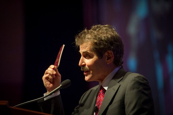 John Stossel holds up a copy of the U.S. Constitution as he offers remarks during the evening banquet as part of the 30th anniversary celebration of The Washington Times at the Marriott Wardman park Hotel in Washington, D.C., Tuesday, October 2, 2012. (Rod Lamkey Jr./The Washington Times)